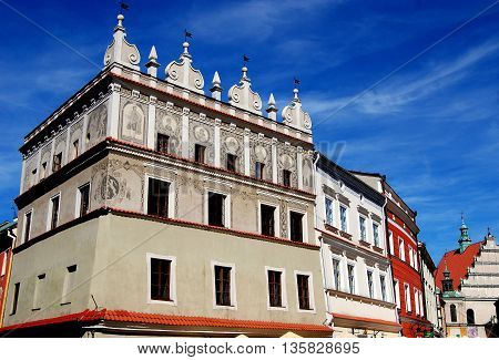 Lublin Poland - June 5 2010: A flamboyantly baroque building with fresco decorations on the top story in the handsome Rynek Market Square