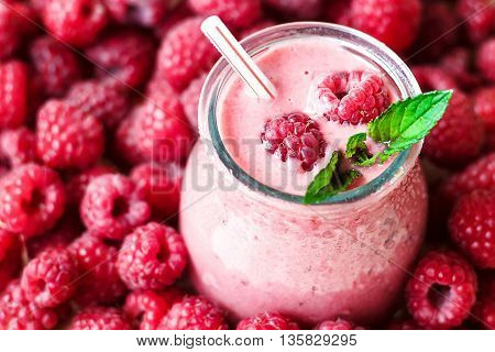 Beautiful appetizer pink raspberries fruit smoothie. Yogurt cocktail. Close up. Natural detox. Liquid ice cream. Glass of raspberry milk shake with berries background, top view.