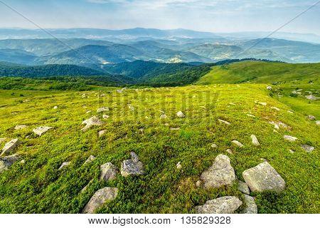 white sharp boulders on the green hillside