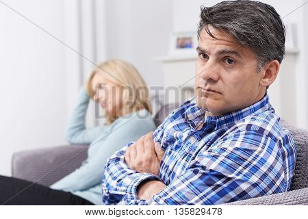 Couple With Relationship Difficulties Sitting On Sofa