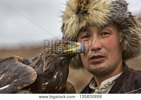 ISSYK KUL, KYRGYZSTAN - MAY 29, 2016: Eagle hunter holds the golden eagle and looks at me.