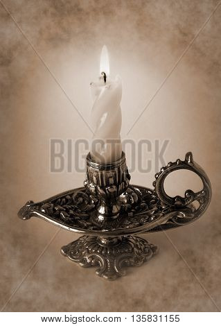 Photo shows the bronze candlestick with burning candle - Sepia toned artwork in retro style