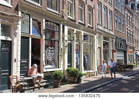 AMSTERDAM, NETHERLANDS - MAY 8, 2016: Typical street in 'The Nine Streets'- special neighbourhood is full with vintage and designer shopping speciality stores and cosy cafes, Amsterdam. Amsterdam is a capital and the largest city of Netherlands.