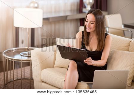 Nice work. Happy beautiful young woman looking down and taking notes while sitting on the sofa near an open laptop