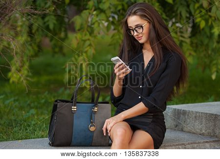 Portrait of a woman sending text message from her phone. Happy beautiful woman walking and writing or reading sms messages on line on a smart phone
