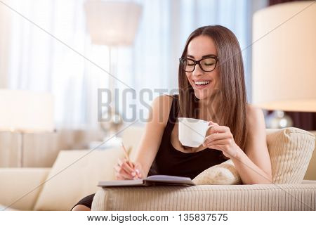 Lets note it. Amazing young brunet woman looking down and taking notes in a notebook while sitting on the sofa and having a cup of coffee
