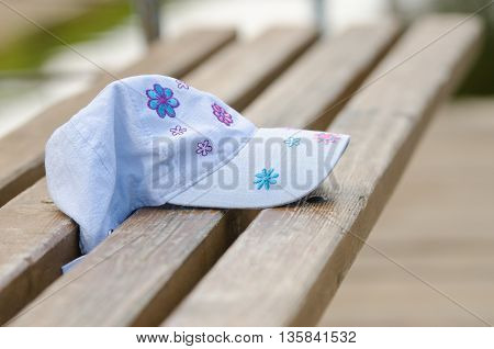 Forgotten cap girl lying on a bench