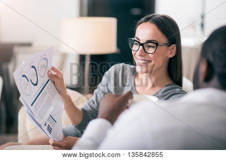 What do you think. Amazing confident business woman showing diagrams to her colleague while sitting