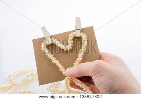 Pearl necklace forms heart shape on paper on white background