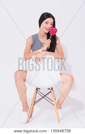 Rise your mood. Cheerful content charming woman holding lollypop and sitting in the chair while expressing joy