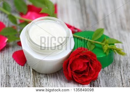 Face and body cream with red rose.Cosmetic jar of face and body cream on wooden board romantic style