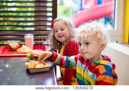 Little girl and boy eating chicken nuggets hamburger and French fries in a fast food restaurant. Child with sandwich and potato chips. Kids eat unhealthy fat food. Fastfood sandwich for children.