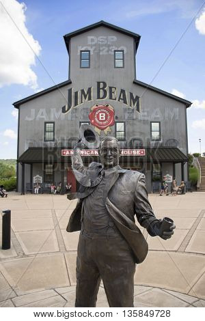 CLERMONT Kentucky USA - June 18 2016: Tourists visit the Jim Beam Stillhouse with a statue of Jim Beam in front of it, on June 18. This is one of the stops on the Kentucky bourbon trail.