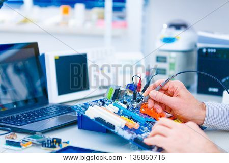Repair motherboard in electronics laboratory. Technological background with closeup on tester checking motherboard. Electronics repair service, hands of female tech fixes an electronic