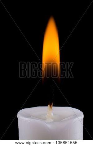burning white candle on a black background