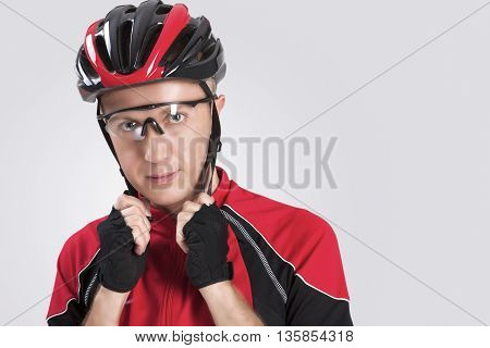 Cycling Safety Concept and Ideas. Portrait of Male Caucasian Cyclist Putting On Helmet. Against White Background. Horizontal Image