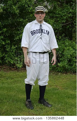 OLD BETHPAGE, NEW YORK - MAY 22, 2016: Baseball player in 19th century vintage uniform during old style base ball play following the rules and customs from 1864 in Old Bethpage Village Restoration