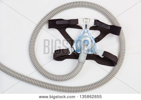 Sleep apnea CPAP mask and hose on white pillow background to use with CPAP machine for people with sleep apnea or sleep disorder