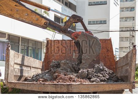 Excavator or sand into truck body. select focus on excavator.