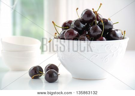 Dark Lapin cherries in white bowl in horizontal format