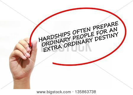 Man writing HARDSHIPS OFTEN PREPARE ORDINARY PEOPLE FOR AN EXTRA ORDINARY DESTINY with marker on transparent wipe board.