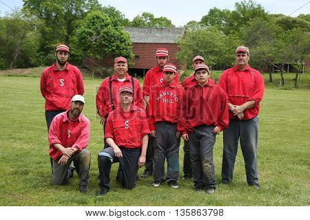 OLD BETHPAGE, NEW YORK - MAY 22, 2016: Baseball team in 19th century vintage uniform during old style base ball play following the rules and customs from 1864 in Old Bethpage Village Restoration