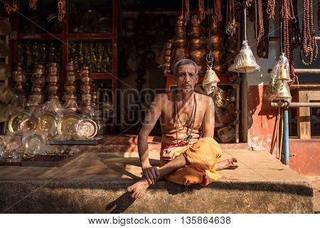 Gokarna, India - January 16, 2016: Unidentified temple brahmin sitting in his shop in Gokarna. The city is a holy pilgrimage site for Hinduists