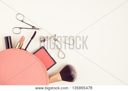 Top view of pink cosmetic bag consist of makeup brush lipstick brush on scissors mascara eyelash curler on white background - vintage filter tone poster