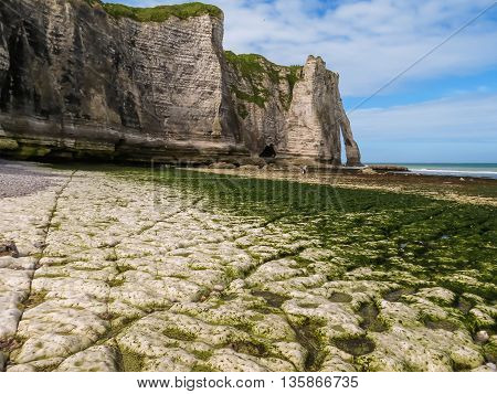 The coast of English Channel in outflow and cliff Porte d'Aval as background. Etretat, Normandy, France