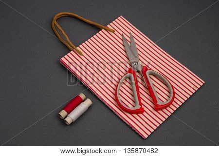 Grey And Red Thread, Scissors And Striped Gift Pack On Grey Background