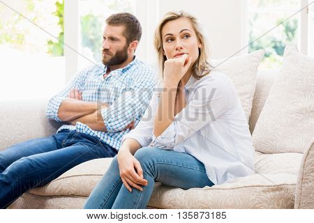 Young couple ignoring each other in living room at home