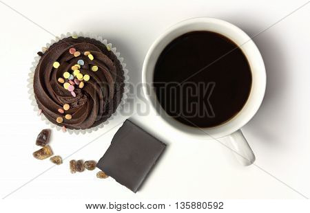 A photo of a cup of black coffee and a chocolate cupcake with pieces of cane sugar and an ounce of chocolate shot from above on white background