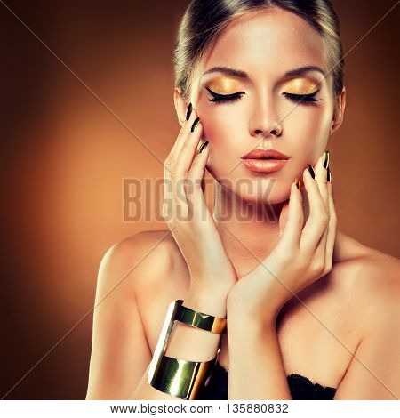 Girl with the Golden makeup and metal nails. Cosmetics, beauty and fashion.