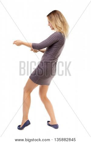 back view of standing girl pulling a rope from the top or cling to something. Rear view people collection.  backside view of person.  Isolated over white background. Blonde in a short dress pulls rope