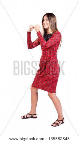 skinny woman funny fights waving his arms and legs. Rear view people collection.  backside view of person.  Isolated over white background. The girl in red plaid dress smiling to become boxing stance