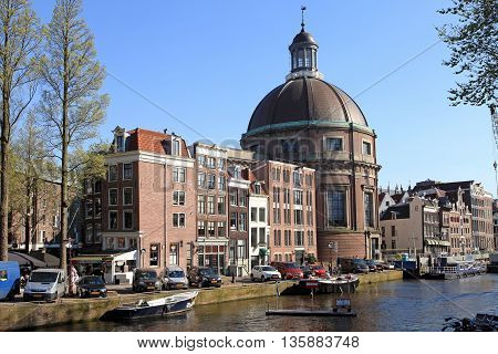 AMSTERDAM, NETHERLANDS - MAY 8, 2016: View of traditional houses and boats on Singel canal in Amsterdam, Netherlands. Amsterdam is capital and most populous city of Netherlands