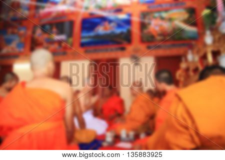 Blurred abstract image of Newly ordained Buddhist monk inside temple.