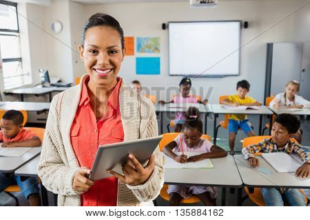 Teacher posing in front of class with tablet pc at elementary school
