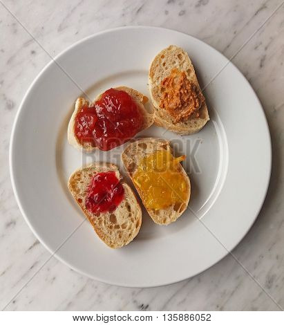 Bread slices with orange marmalade strawberry jam redberry jam and peanut butter poster