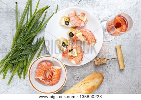Tasty various italian sandwiches with seafood against rustic wooden background. Crostini with cheese king shrimps lemon sliced olives on white plate glass of wine herbs and bread horizontal top view