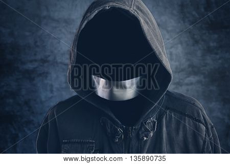 Unrecognizable hooded hooligan with mouth duct taped spooky faceless criminal person in jacket with hood