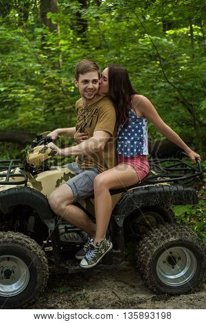 Young couple hugs kisses and smiles on forest road while driving a quad bike on a summer day. Young man and woman on an ATV