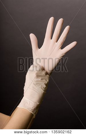 Female hands in golves. Doctor or nurse putting on latex gloves. Sanitary, healthcare, medical clothing. Dark background