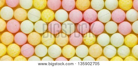 Yummy sugar pearls or bubble gum close up horizontal background