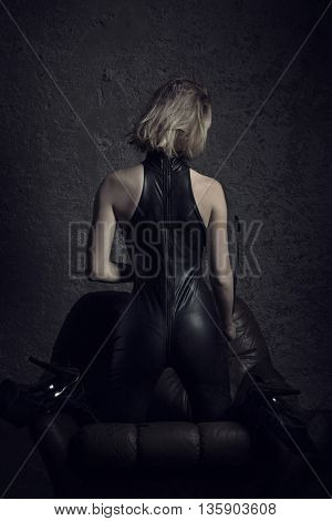 Sexy woman in latex catsuit kneeling on sofa bdsm