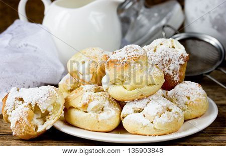 Cream puffs filled vanilla custard and sugar powder icing traditional French cuisine selective focus