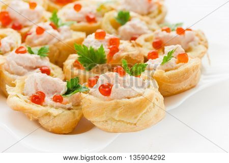 Cocktail snack with red caviar. Tartlets of choux dough with salmon mousse and red caviar on a white plate close up selective focus