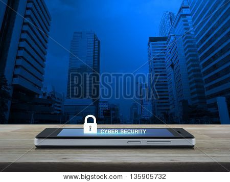 Key icon and cyber security text on modern smart phone screen on wooden table in front of city tower background Cyber security concept
