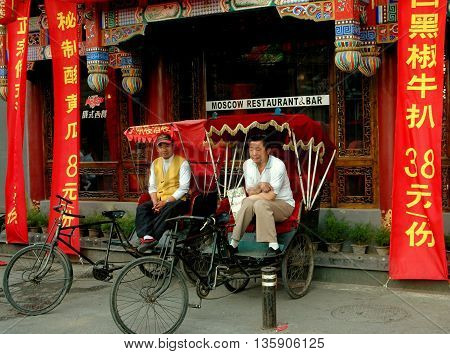 Beijing China - May 5 2005: Two pedicab drivers in their taxis waiting for fares in front of a restaurant & bar at the Shi Sa Hai Hutong