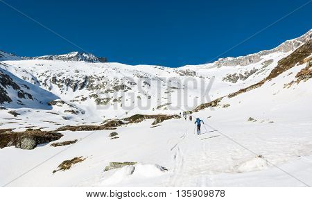 Skiers ascending a mountain slope. Ski touring in Malta valley, Austria.